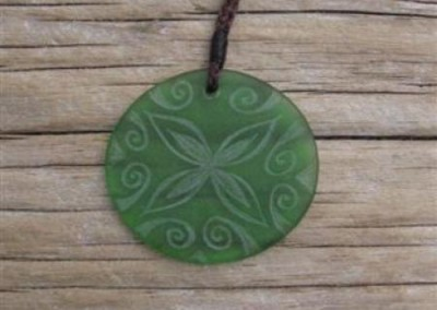 Tapa flower design with koru border engraved glass oval pendant $70 PALE GREEN Colours available - amber, orange, light red, dark red, pale green, lime green, mid-green, dark green, moss green, aqua green, turquoise blue, sapphire blue, teal blue, cobalt/dark blue, pale lavender, purple