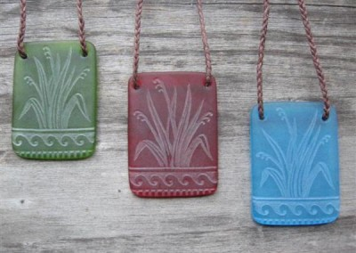 Harakeke/flax design engraved glass pendant. $72. LIGHT GREEN; LIGHT RED; TURQUOISE BLUE. Colours available - amber, orange, light red, dark red, pale green, lime green, mid-green, dark green, moss green, aqua green, turquoise blue, sapphire blue, teal blue, cobalt/dark blue, pale lavender, purple.