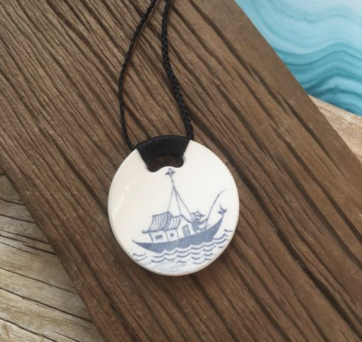 This pendant has been handcrafted from broken/recycled china, and is formed into a rectangle shape. It measures approximately 5 cm high and 3.6 cm wide. The cord is plaited and is attached to the pendant using a unique binding method. The length of the cord is approximately 50 cm; it is designed to sit just below the collar bone. It fastens with a simple loop and toggle system; the toggle matching the china of the pendant. This pendant features a small segment of the classic Crown Lynn pattern 'Ponui' and comes from a dinner plate made during the period between 1969 and 1975. The base colour is a subtle combination of teal blue and sage green, with a stylised geometric black lace pattern on top. This piece has a slight curve due to its position on the plate. This piece is made up with a black cord; please choose black cord in the box below
